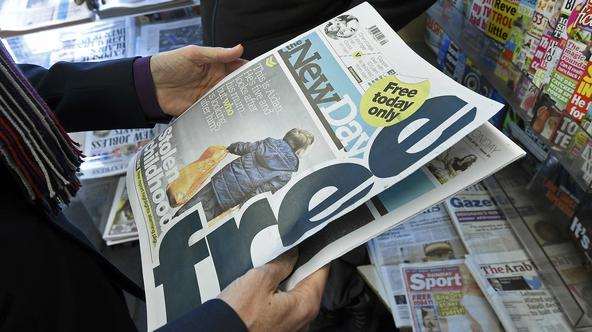 A customer holds a copy of the New Day at a newsagents in central London, Britain February 29, 2016. The new national newspaper launched on Monday. REUTERS/Toby Melville