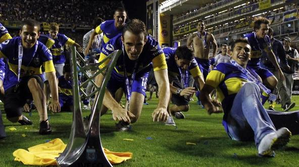 'Boca Juniors\' Leandro Somoza (C) and teammates celebrate with the trophy at the end of their Argentine First Division soccer match against Banfield in Buenos Aires, December 4, 2011. Boca Juniors wo