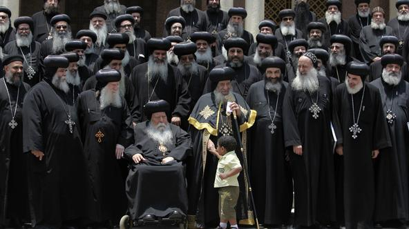 Leader of Egypt's Copts, Pope Shenouda (C), holds the hand of a boy as he stands with heads and representatives of churches, before holding  a news conference at the main cathedral in Cairo June 8, 2010. An Egyptian court has ruled that two Coptic men hav