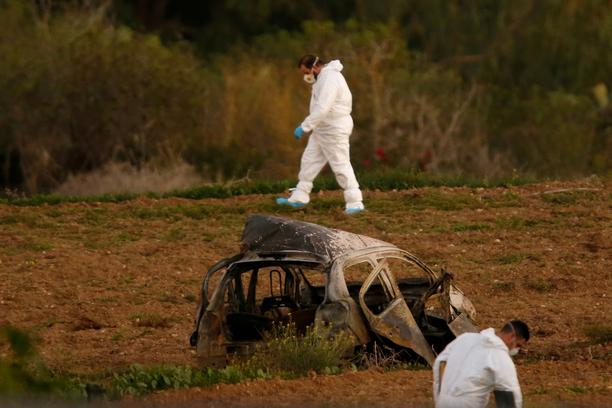 FILE PHOTO: Forensic experts walk in a field after a powerful bomb blew up a car killing investigative journalist Daphne Caruana Galizia in Bidnija