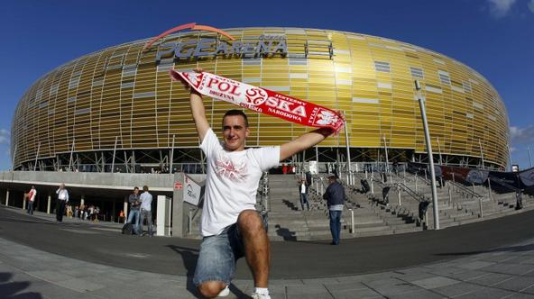 'A fan of Poland\'s soccer team poses with scarf before their international friendly soccer match against Germany outside of the newly built stadium for the Euro 2012 European Championships in Gdansk