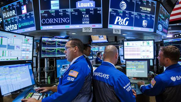FILE PHOTO: Traders work on the floor of the New York Stock Exchange shortly before the closing bell in August 2015