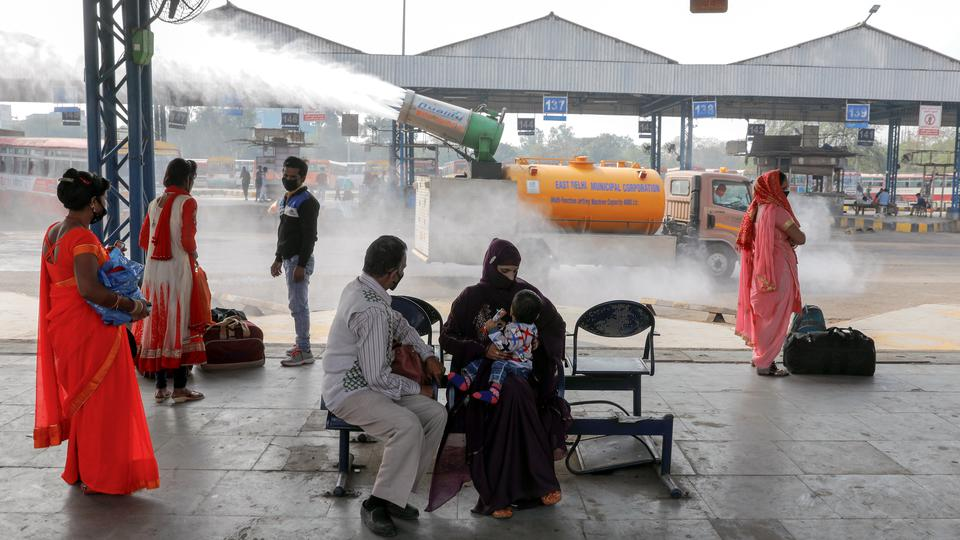 "A municipal worker operates an ""anti-smog gun"" in India's capital as passengers are seen at a bus depot in New Delhi"
