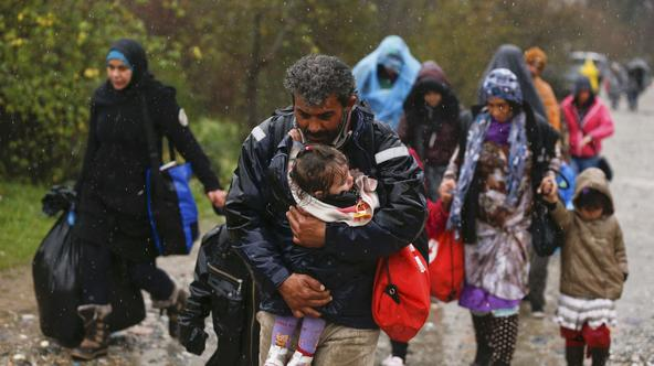 A migrant carries his child after crossing the border from Greece into Macedonia, near Gevgelija, Macedonia, November 27, 2015. Macedonia, Serbia and other Balkan states have implemented a new policy to filter the flow by granting passage onwards toward W