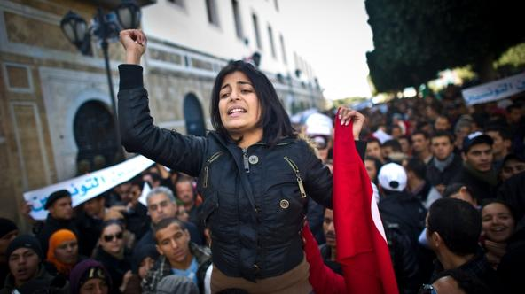 'A woman raises her fist during a demonstration calling on the new government to quit, on Bourguiba avenue in central Tunis on January 22, 2011. Thousands of people rallied in Tunisia today as the pri
