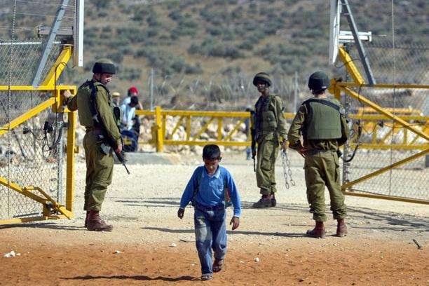 'palestina izrael Israeli soldiers open a gate in the security fence, built by Israel to seperate Israel from the West Bank, for a Palestinian boy returning from school to his village near the West Ba