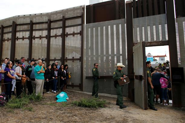 FILE PHOTO: U.S. Border patrol agents stand at an open gate on the fence along the Mexico border to allow Adrian Gonzalez-Morales and his daughter Aileen hug his parents Juan and Martha, as part of Universal Children's Day at the Border Field State Park,