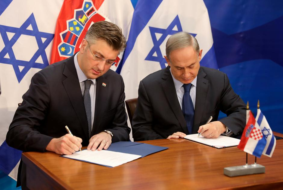 Israeli Prime Minister Benjamin Netanyahu (R) and his Croatian counterpart Andrej Plenkovic sign a bilateral agreement in Jerusalem January 24, 2017. REUTERS/Gali Tibbon/Pool | Autor :