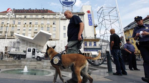 \'A police explosive specialist and his dog patrol Zagreb\'s main square, while workers construct a stage ahead of Pope Benedict XVI\'s visit, June 1, 2011. The Pope will visit Zagreb for the first ti
