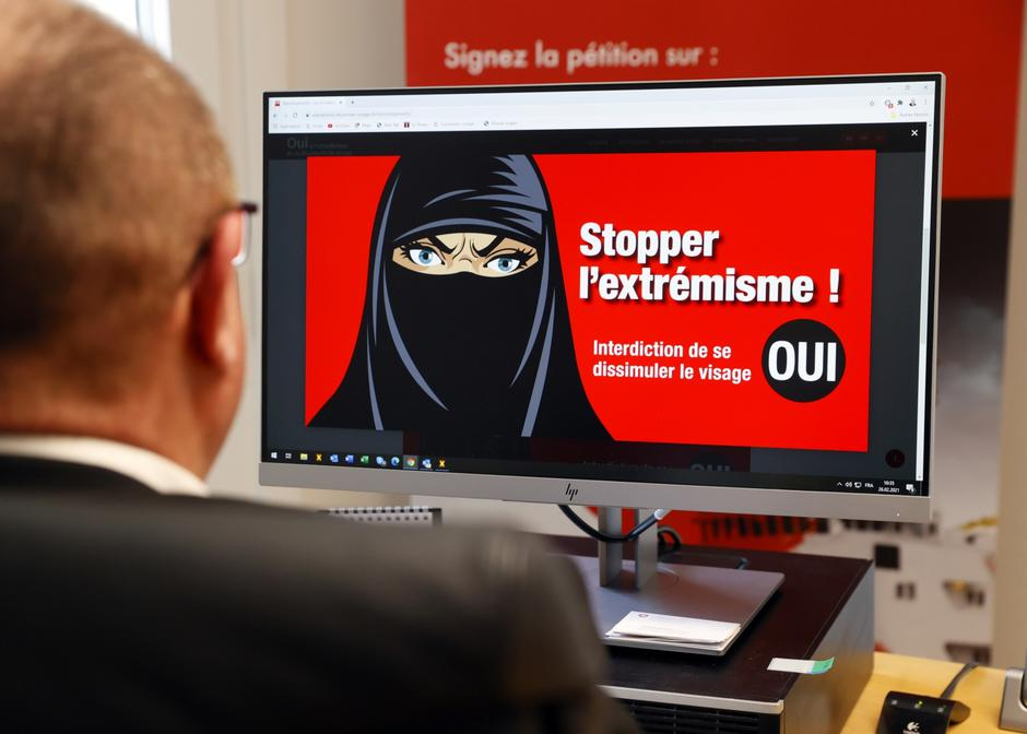 "Swiss National Councillor Addor looks on his computer at a poster reading ""Stop Extremism!"" in Sion 