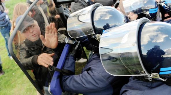 \'Anti riot policemen push demonstrators who block the fuel storage depot of Douchy-Les-Mines, northern France, to protest against French government pensions reform on October 19, 2010.        TOPSHOT