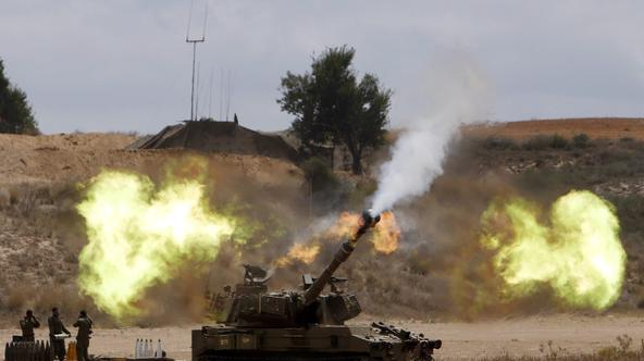 An Israeli mobile artillery unit fires towards the Gaza Strip July 18, 2014. Israel stepped up its ground offensive in Gaza early on Friday pounding targets with artillery fire and using tanks and infantry to battle Hamas fighters. Orange flashes illumina