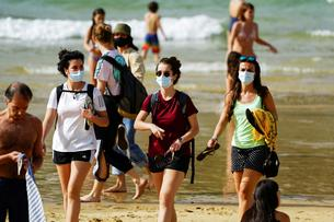 People wear masks at La Concha beach after Spain introduced stricter mask laws during the coronavirus disease (COVID-19) outbreak, in San Sebastian