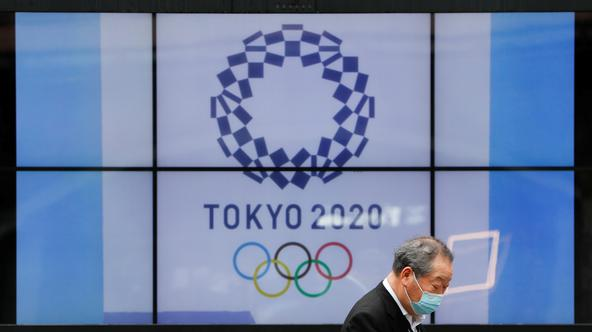 A passerby wearing a protective face mask walks past a screen showing the logo of the Tokyo 2020 Olympic Games in Tokyo