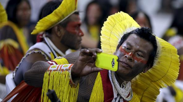 An indigenous man from the Kayapo tribe takes a picture as he arrives to participate in the I World Games for Indigenous People in Palmas, Brazil, October 20, 2015. REUTERS/Ueslei Marcelino