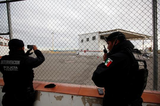 Federal police officers stand at a fence surrounding a private landing strip, as signs of increased security are seen next to the international airport in Ciudad Juarez, Mexico, January 19, 2017. Notorious Mexican drug lord Joaquin