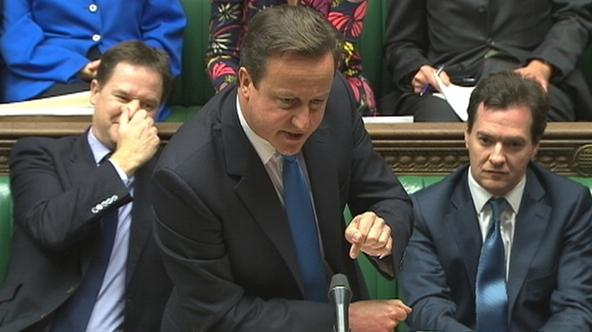'Britain\'s Prime Minister David Cameron, flanked by Deputy Prime Minister Nick Clegg (L), and Chancellor of the Exchequer George Osborne, speaks to parliament during Prime Minister\'s Questions in th