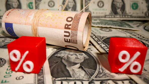 Rolled Euro banknotes and 3D printed percent models are placed on U.S. Dollar banknotes