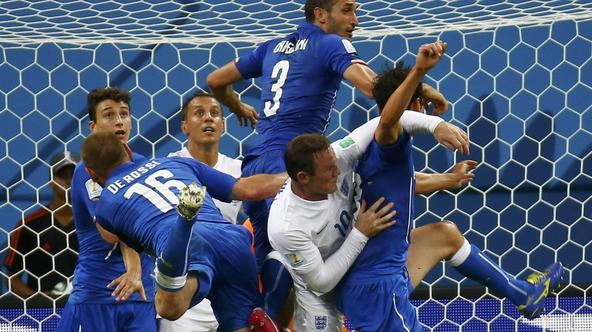 Italy's Daniele De Rossi (16), Giorgio Chiellini (3) and teammates jump for the ball against England's Wayne Rooney (10) and Phil Jagielka during their 2014 World Cup Group D soccer match at the Amazonia arena in Manaus June 14, 2014. REUTERS/Kai Pfaffenb