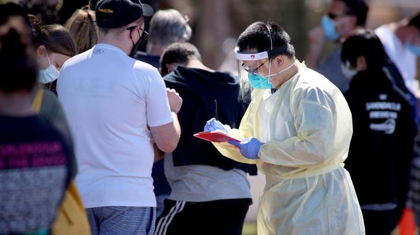 A medical staff member takes details from people queuing at a COVID-19 testing site in Adelaide