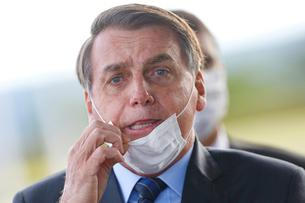 FILE PHOTO: Brazil's President Jair Bolsonaro adjusts his mask as he leaves Alvorada Palace, amid the coronavirus disease (COVID-19) outbreak in Brasilia