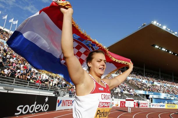 'Sandra Perkovic of Croatia poses with her national flag after winning the women's discus final at the European Athletics Championships in Helsinki July 1, 2012.     REUTERS/Dominic Ebenbichler (FINL