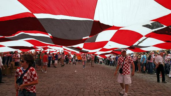 Croatian supporters walk under a large flag before the Euro 2012 soccer match between Croatia and Ireland in Poznan June 10, 2012.  REUTERS/Kacper Pempel (POLAND  - Tags: SPORT SOCCER)  Picture Supplied by Action Images