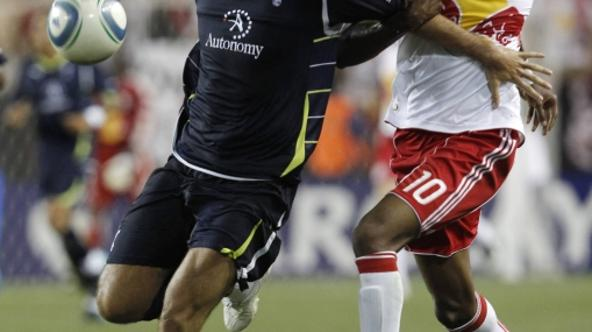 'Verdan Corluka of Tottenham Hotspur (L) controls the ball away from Macoumba Kandji of Major League Soccer\'s New York Red Bulls during the second half of their game at Red Bull Arena in Harrison, Ne