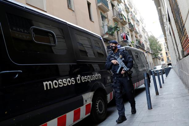 A police officer stands guard on the street as the intervention in a drug bust takes place in the El Raval neighbourhood of Barcelona