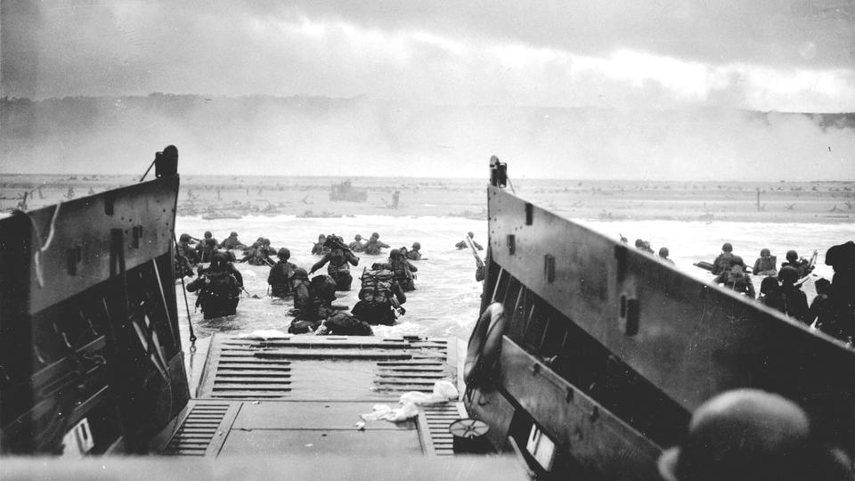 U.S. troops wading ashore from a Coast Guard landing craft at Omaha Beach during the Normandy D-Day landings near Vierville sur Mer