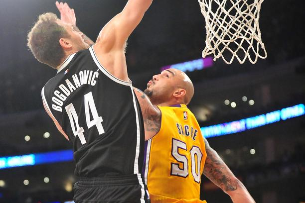 February 20, 2015; Los Angeles, CA, USA; Brooklyn Nets guard Bojan Bogdanovic (44) dunks to score a basket against the defense of Los Angeles Lakers center Robert Sacre (50) during the first half at Staples Center. Mandatory Credit: Gary A. Vasquez-USA TO