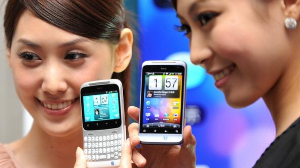 \'A woman displays an HTC \'ChaCha\' (L) mobile phone during a press conference in Taipei on July 14, 2011. The model is expected to hit the local market late July with a price tag of 342 USD. AFP PHO