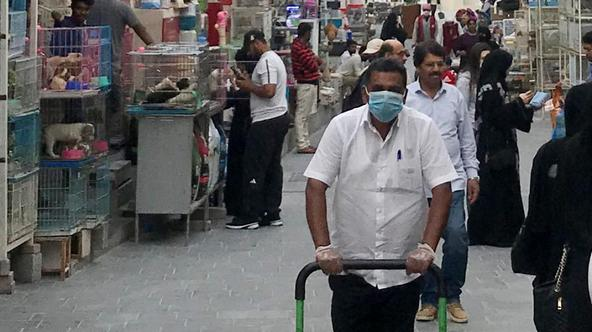 A man wears a protective face mask, following the outbreak of coronavirus, as he pushes a cart in souq Waqif in Doha