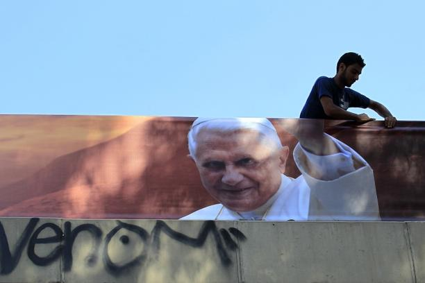 'A worker hangs a banner bearing the picture of Pope Benedict XVI in Dora, north Beirut, on September 6, 2012 ahead of the pope's visit on September 14-16. Security forces have been placed on alert a