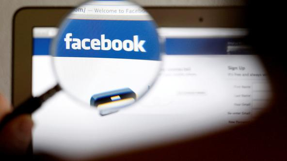 FILE PHOTO: In this photo illustration, a Facebook logo on a computer screen is seen through a magnifying glass held by a woman in Bern