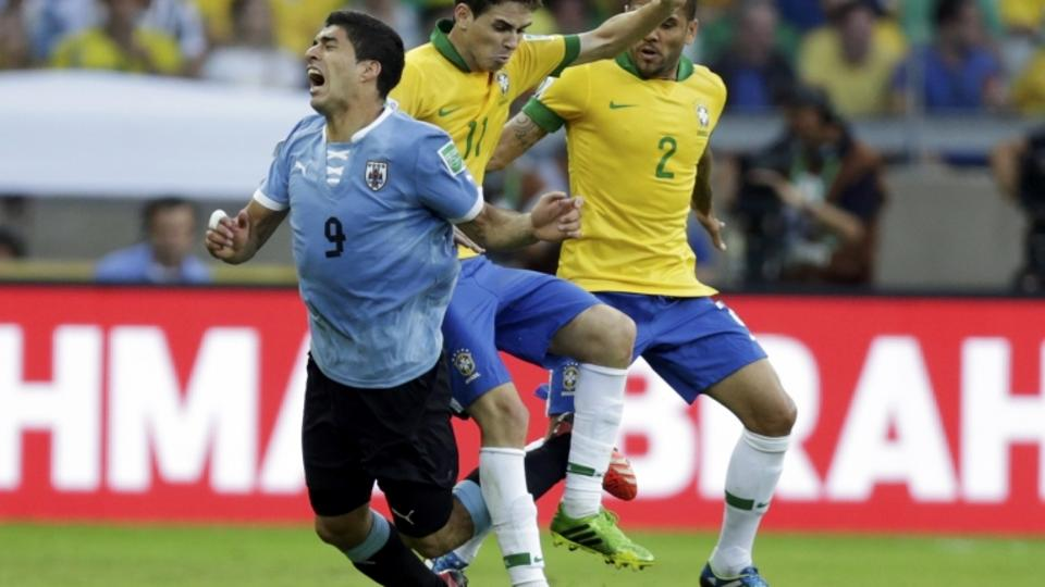'Uruguay's Luis Suarez (L) reacts as he is challenged by Brazil's Oscar and Dani Alves (R) during their Confederations Cup semi-final soccer match at the Estadio Mineirao in Belo Horizonte June 26,