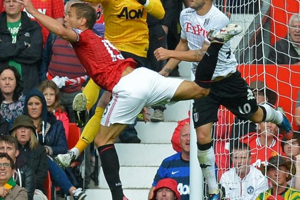 'Manchester United\'s Spanish goalkeeper David de Gea (2nd L) punches the ball under pressure from Fulham\'s Croatian striker Mladen Petric (R) and Manchester United\'s Serbian defender Nemanja Vidic