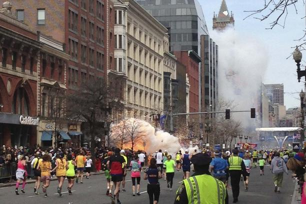 'Runners continue to run towards the finish line of the Boston Marathon as an explosion erupts near the finish line of the race in this photo exclusively licensed to Reuters by photographer Dan Lampar