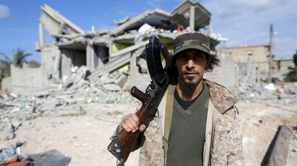 Member of East Libyan forces holds his weapon as he stands in front of a destroyed house in Ganfouda district in Benghazi A member of East Libyan forces holds his weapon as he stands in front of a destroyed house in Ganfouda district in Benghazi, Libya, J
