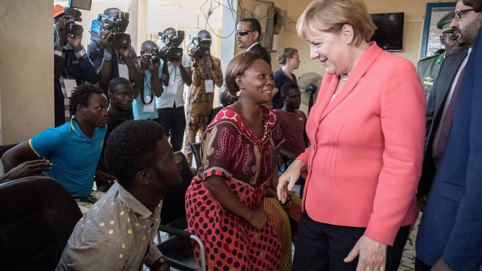 German Chancellor Angela Merkel (CDU) inside a reception and transit center for migrants of the International Organization for Migrants (IOM) speaking with refugees such as Liberian Binta (M) in Niamey, Niger, 10 October 2016. Chancellor Merkel is on a th