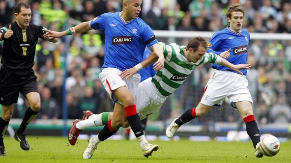 'Celtic\'c Aiden McGeady (C) falls forward as Rangers\' Madjid Bougherra (L) challenges during their \'Old Firm\' soccer match at Ibrox stadium in Glasgow, Scotland February 28, 2010. REUTERS/David Mo