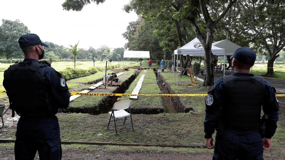 Police officers keep watch as employees work to exhume bodies at a private cemetery as part of a search for victims of the 1989 invasion by the U.S. military action to topple strongman Manuel Noriega, in Panama City