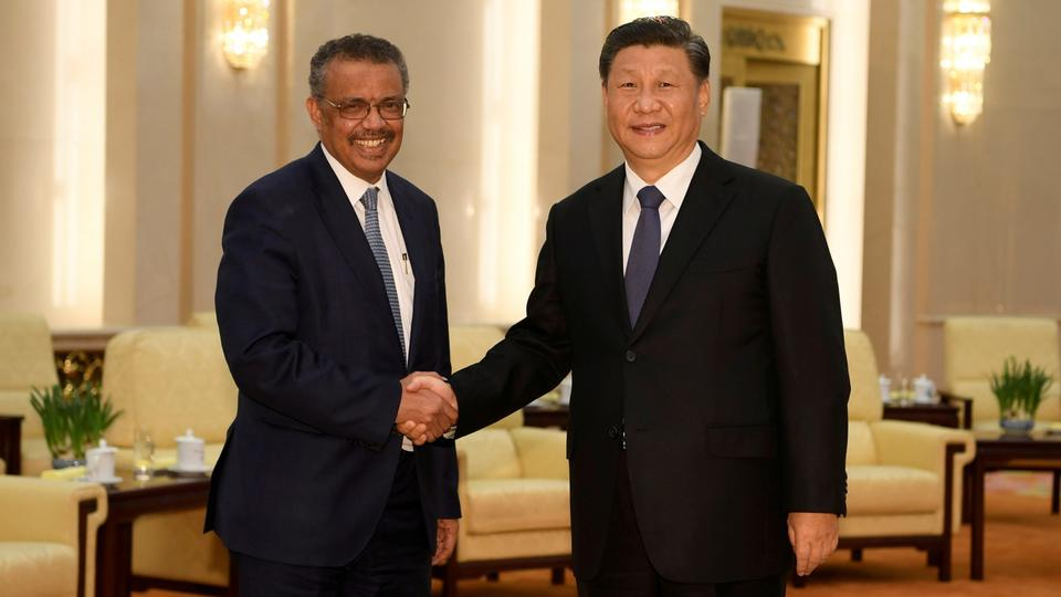 FILE PHOTO: Tedros Adhanom, director general of the World Health Organization, shakes hands with Chinese President Xi jinping before a meeting at the Great Hall of the People in Beijing