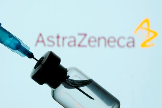 FILE PHOTO: Vial and sryinge are seen in front of displayed AstraZeneca logo
