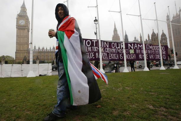 A pro-Palestine supporter wears a Palestinian and Union flag outside the Houses of Parliament in London October 13, 2014.  British Prime Minister David Cameron will not take part in a parliamentary vote on whether the government should recognise Palestine