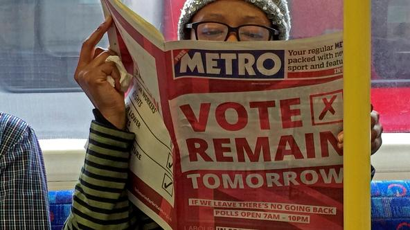 REFILE - ENHANCING QUALITY A woman reads a newspaper on the underground in London with a 'vote remain' advert for the BREXIT referendum, Britain June 22, 2016. REUTERS/Russell Boyce