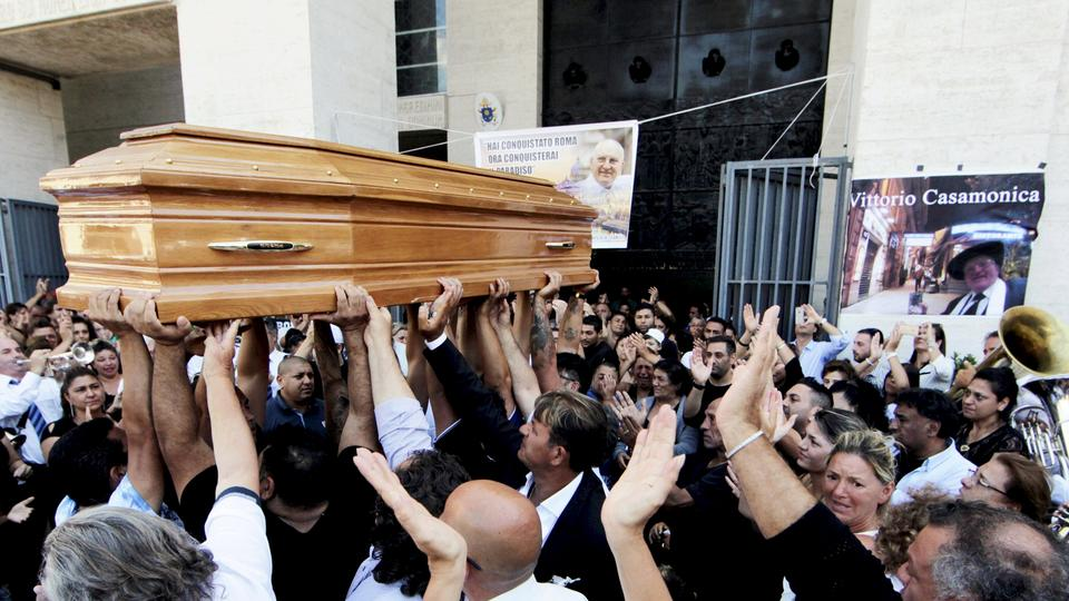 People carries the body of Vittorio Casamonica into a Roman Catholic basilica in a Rome suburb, where the funeral mass was celebrated, August 20, 2015. Casamonica, 65, the head of a notorious Rome crime family, was given a lavish funeral on Thursday, with